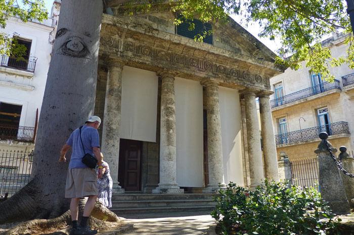 Turistas dando la vuelta a la ceiba dentro de El Templete de La Habana