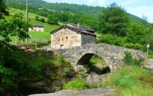Cabaña pasiega junto a un puente sobre el río Yera